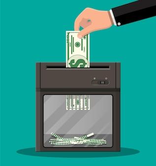 Mão, colocando notas de dólar na máquina trituradora.