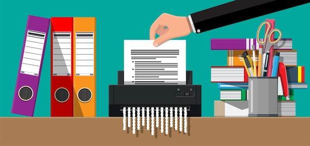 Mão colocando papel de documento na máquina trituradora
