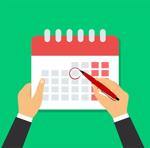 Mão com caneta marca um dia agendado no calendário.