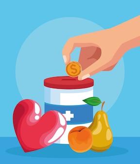 Mão com moedas, lata de doação e frutas sobre azul