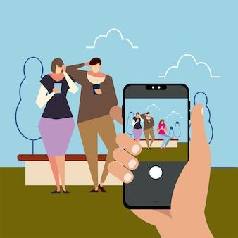 Mão com smartphone tirando uma foto de pessoas usando smartphones na ilustração vetorial parque