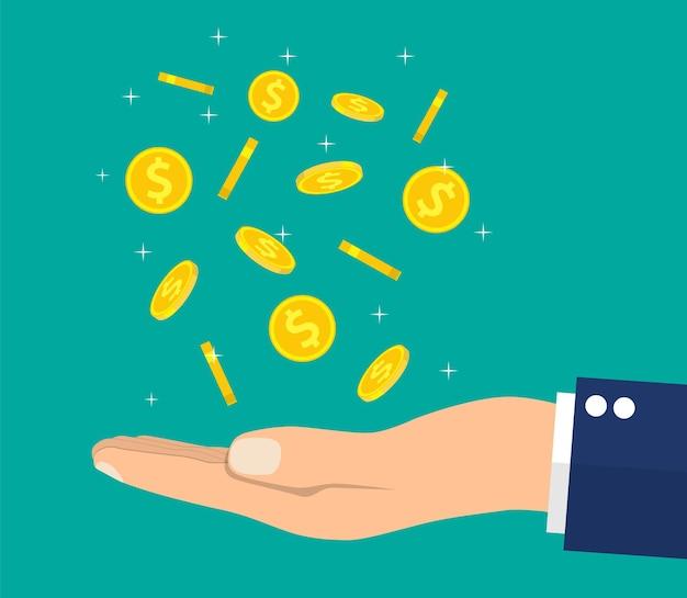 Mão de buisnessman pegando moedas de ouro caindo