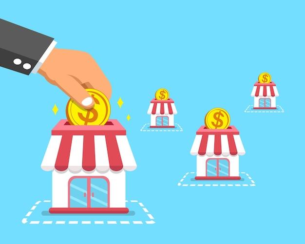 Mão de conceito de negócio de franquia colocando moedas nas lojas
