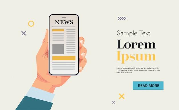 Mão de empresário segurando o celular lendo notícias ou artigos na tela do smartphone