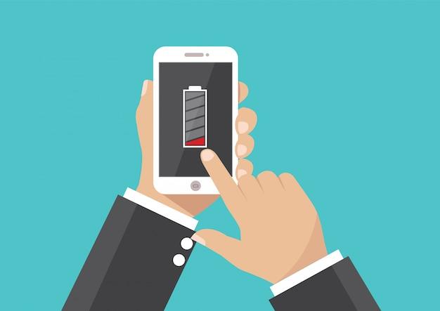 Mão de empresário segurando smartphone com bateria fraca na tela