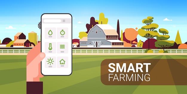 Mão de fazendeiro segurando a condição de monitoramento de smartphone controlando produtos agrícolas organização de colheita conceito de agricultura inteligente edifício agrícola paisagem cópia espaço