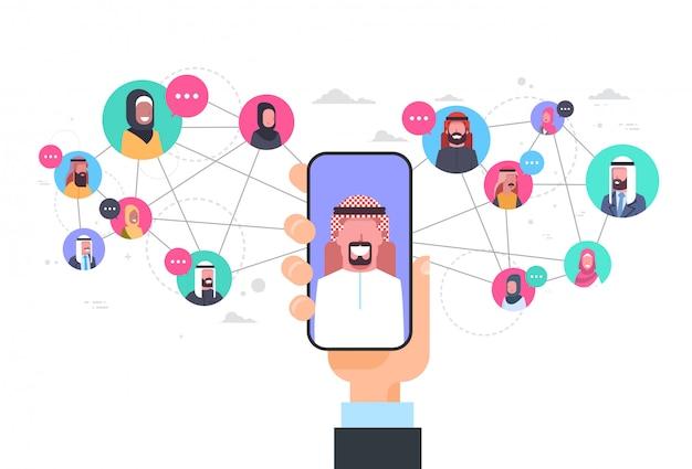 Mão de homem árabe segurando o conceito de comunicação de rede de telefone inteligente grupo de conexão de pessoas árabe