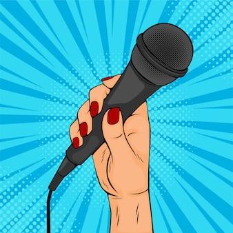 Mão de menina ou mulher segurando a ilustração vetorial de desenho de microfone no estilo cômico retro pop art