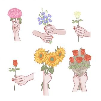 Mão de mulher segurando o conjunto de flores