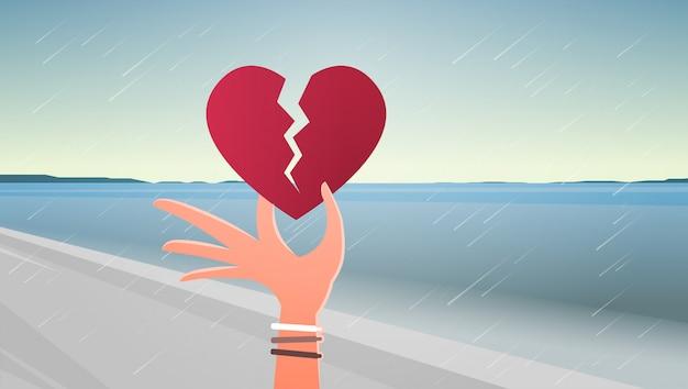 Mão de uma mulher segurando o coração partido
