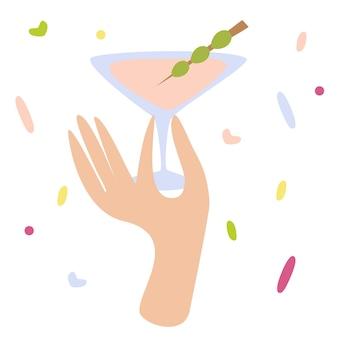 Mão de uma mulher segurando uma taça de coquetel com martini ou bebida alcoólica com azeitona happy hour