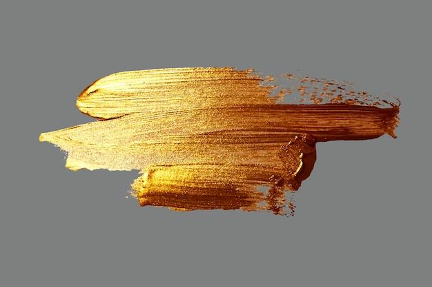 Mão desenhando uma mancha dourada de pincelada em um fundo cinza, ilustração
