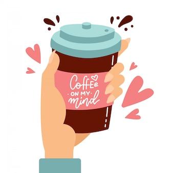 Mão do cliente segurando a xícara de café de papel com pictogramas de coração de amor. ilustração dos desenhos animados plana cofee na minha mente, citação de letras.