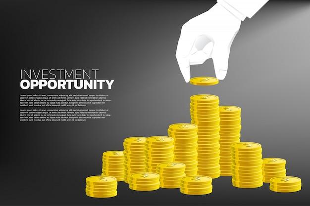 Mão do empresário com moedas e pilha de moedas de ouro.