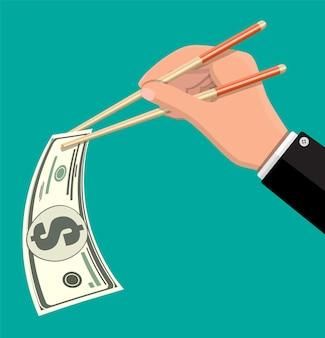 Mão do empresário com pauzinhos com notas de dólar. conceito de dinheiro de poupança, doação, pagamento. símbolo de riqueza.