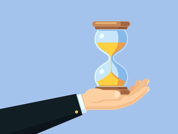 Mão do homem de negócios dos desenhos animados que prende o hourglass antigo. conceito de negócio de vetor de gerenciamento de tempo com relógio de areia