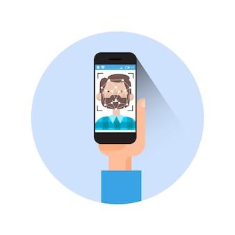 Mão do ícone que guarda o conceito de sistema moderno da identificação da cara do homem da exploração do telefone