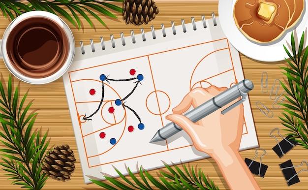 Mão escrevendo o plano de basquete perto do fundo da mesa com panqueca e alguns adereços de folhas