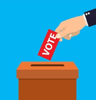 Mão humana colocando papel de votação