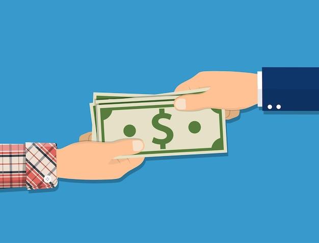 Mão humana dando dinheiro a outra mão.