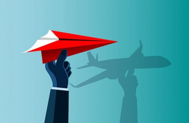Mão humana pegando um avião de papel vermelho com uma sombra na parede como um avião