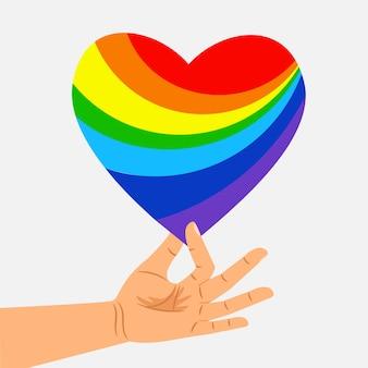 Mão humana segura coração arco-íris. conceito lgbt