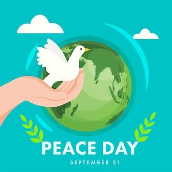 Mão humana segurando o pombo com folhas de oliveira e globo terrestre em fundo turquesa para o dia da paz, 21 de setembro.