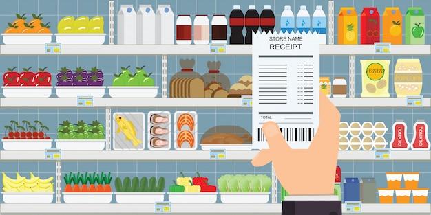 Mão humana segurando o recibo de compras de supermercado.