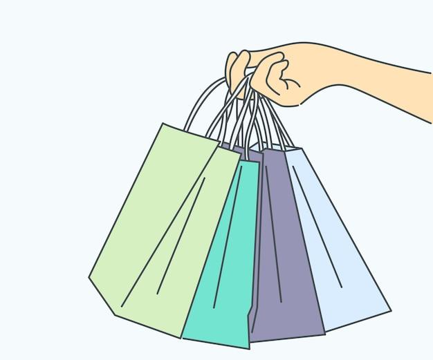 Mão humana segurando sacolas de compras
