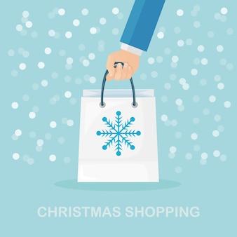 Mão humana segure sacolas de compras com flocos de neve. natal, liquidação de ano novo