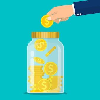 Mão joga uma moeda de ouro na jarra