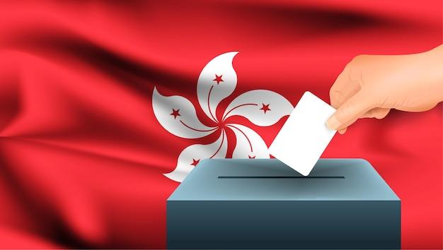 Mão masculina pousa uma folha de papel branca com uma marca como símbolo de um boletim de voto no fundo da bandeira de hong kong.