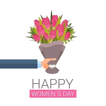 Mão masculina que guarda o ramalhete do conceito do feriado do dia das mulheres felizes das tulipas