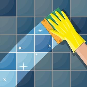 Mão nas luvas com esponja de lavar a parede