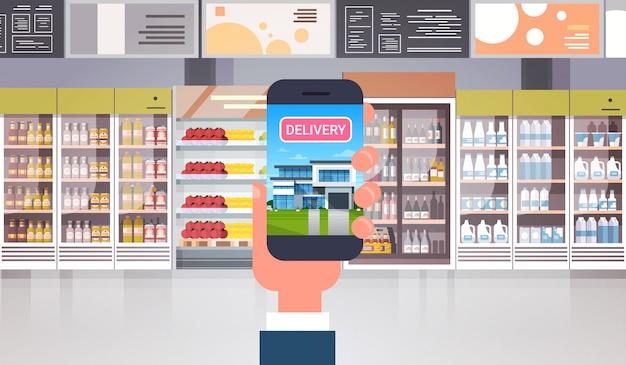 Mão que guarda o telefone esperto no conceito da compra de alimento da entrega dos produtos do mantimento da ordem do supermercado