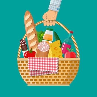 Mão segura a cesta de piquenique wicker cheia de produtos.