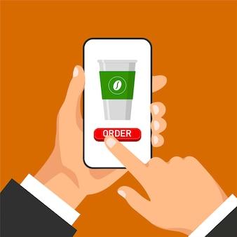 Mão segura o smartphone e pedidos café online. copo de café na tela. o homem clica na tela do telefone.