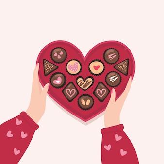 Mão segurando a caixa de forma de coração com chocolate, biscoitos.