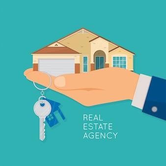 Mão segurando a chave e a casa