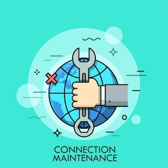 Mão segurando a chave inglesa ou chave inglesa contra globo ex sinal cruzado no fundo.