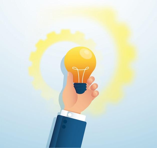 Mão segurando a luz blub. conceito criativo