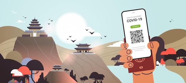 Mão segurando certificado de vacinação digital e passaporte de imunidade global conceito de imunidade de coronavírus chinês edifícios tradicionais ilustração vetorial horizontal