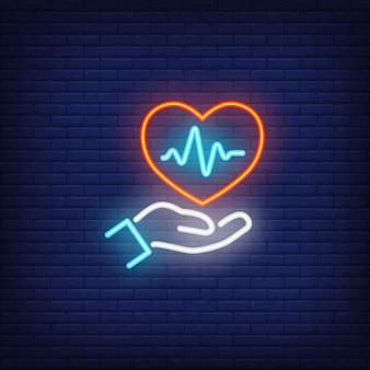 Mão segurando coração com sinal de néon de eletrocardiograma