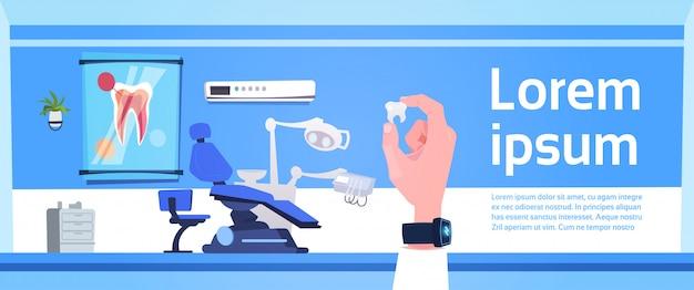 Mão, segurando, dente, sobre, dental, escritório, interior, odontólogo, hospitalar