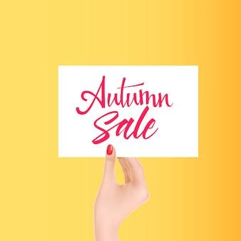 Mão segurando o cartão branco com letras de venda outono