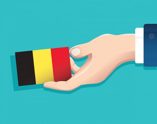 Mão segurando o cartão de bandeira da bélgica