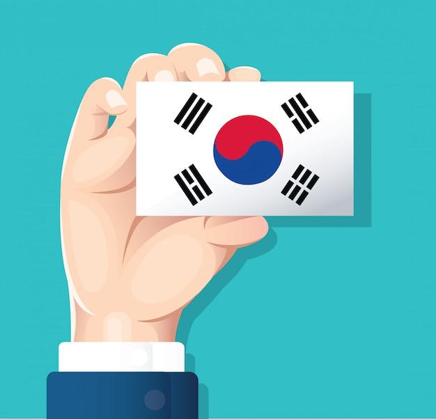 Mão segurando o cartão de bandeira da coreia do sul