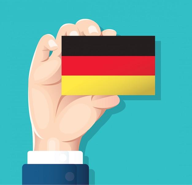 Mão segurando o cartão de bandeira de alemanha