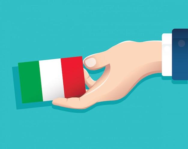 Mão segurando o cartão de bandeira de itália