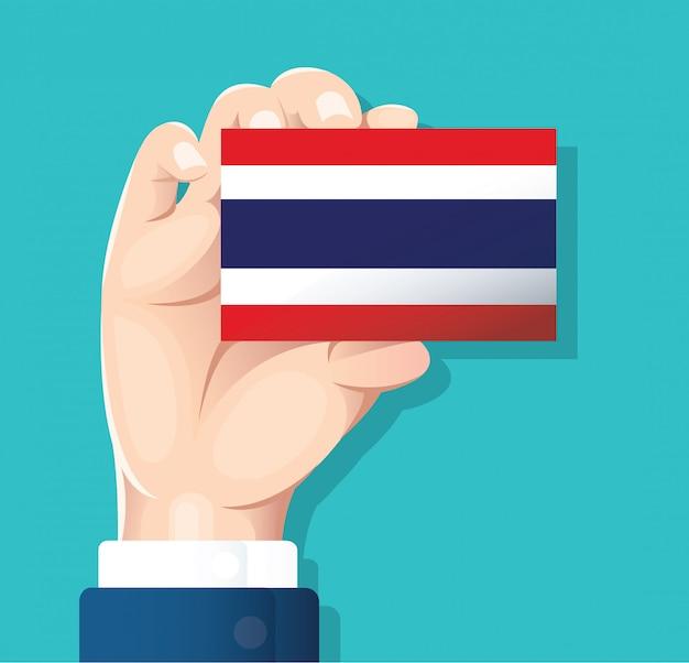 Mão segurando o cartão de bandeira de tailândia